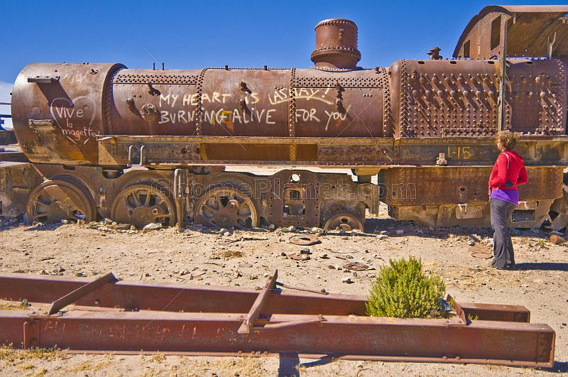 Woman looks at abandoned steam locomotive in the cemetery of steam engines.