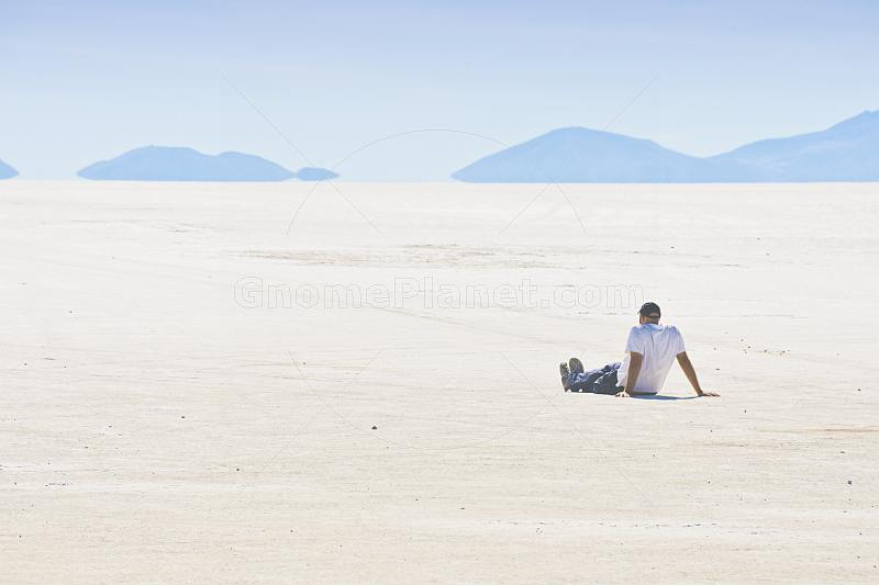Man sits on the Uyuni Salt Flats to admire the view.