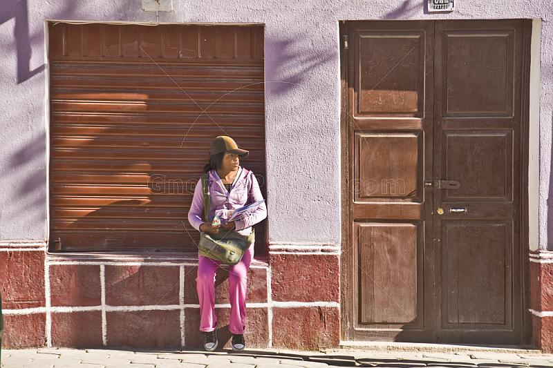 Woman in hat sits on a window cill in the Avenida Potosi.