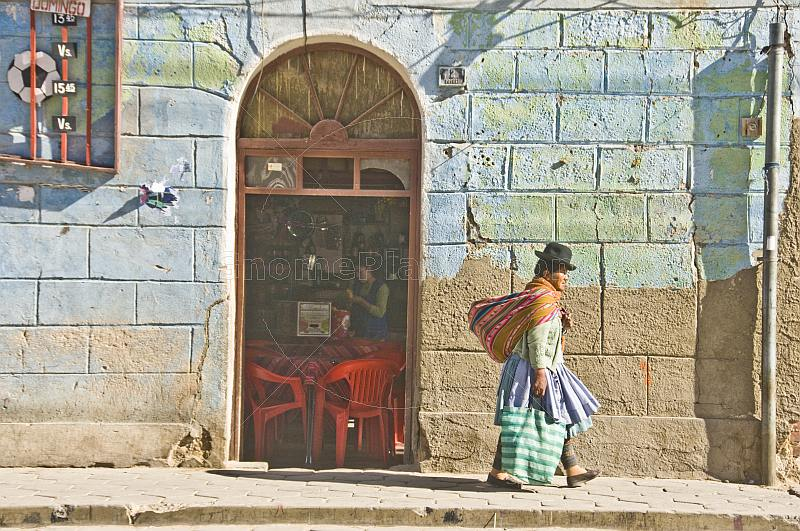 Woman in bowler hat and local dress walks past a cafe on the Avenida Potosi.