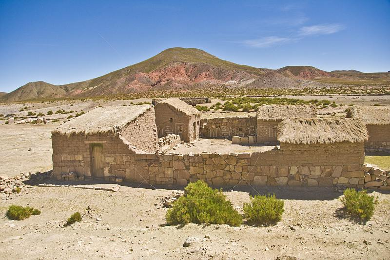 Stone and adobe homestead in a dry and dusty valley.