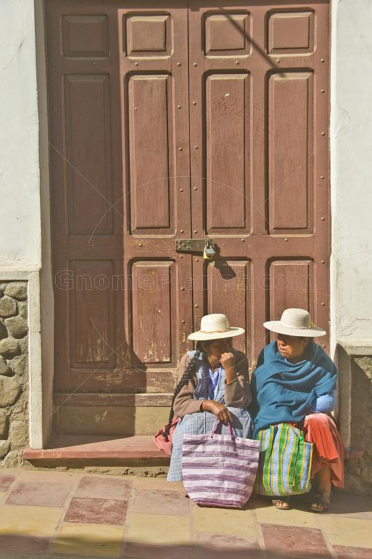 Two women with hats sit on a door step outside a locked brown door.