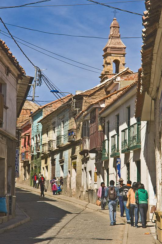 Shoppers walk along Bustillos Street with old colonial houses.