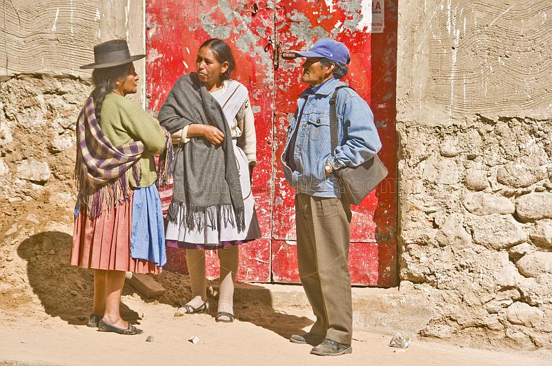 Man and two traditionally dresses Bolivian women talk outside a red door.