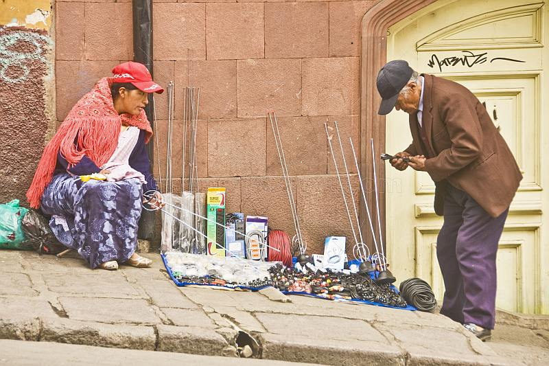 Man buys some TV antenna spares from a female street vendor.