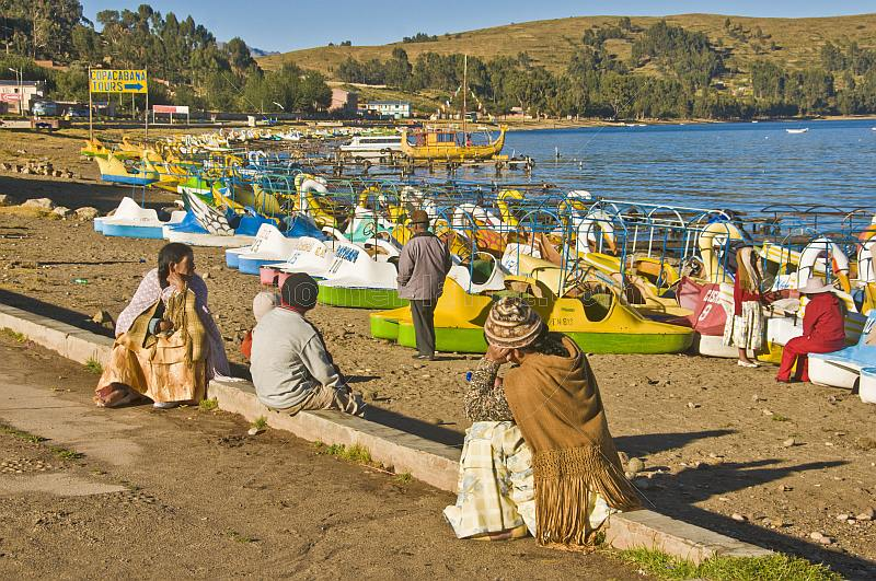 Locals look at a jumble of pedalos pulled up on the beach of Lake Titicaca.