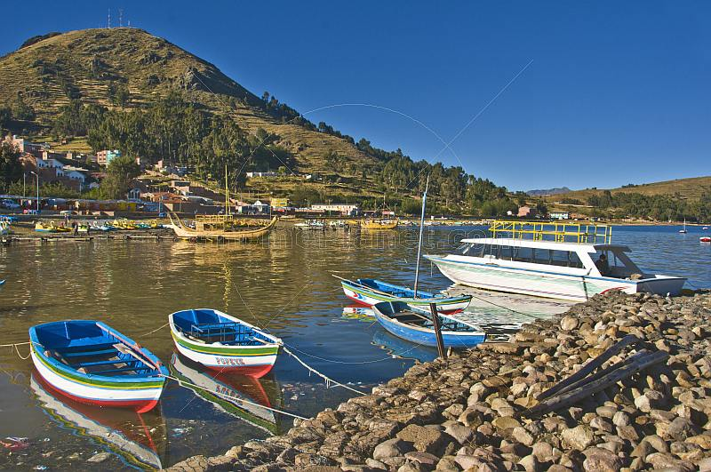 Boats moored on the breakwater and a view of the shore of Lake Titicaca.
