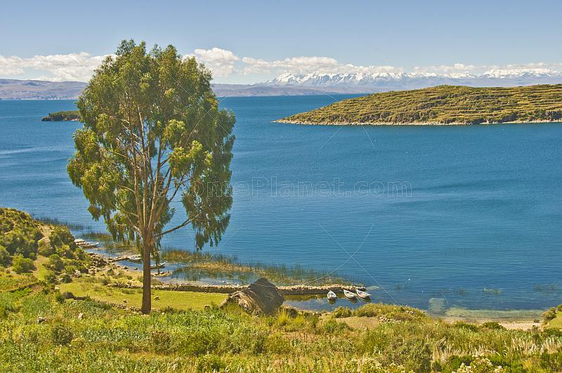 Boats in deserted bay on the Isla del Sol in Lake Titicaca with distant Andes mountains.