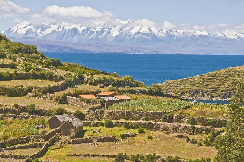 Red-roofed houses and walled bean fields on the Isla del Sol in Lake Titicaca with distant Andes mountains.