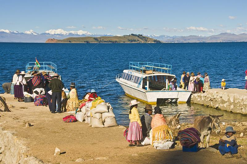 Traditionally dressed locals unload a boat on the Isla del Sol in Lake Titicaca.