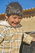 Laughing Bolivian boy in check jacket.