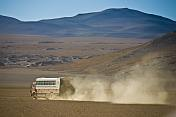 Dragoman Overland truck drives across dusty gravel valley.