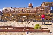 Woman looks at rusting steam locomotive in the cemetery of steam engines.
