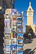 A rack of postcards with Clock Tower in the background.