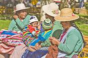 Bolivian women in hats with colorful babies.