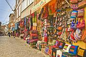 Fabrics and knitwear for sale in a street of souvenirs.