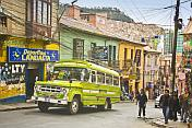 A bus climbs a steep street covered with many electric cables.