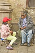 Old man talks to young girl in a red hat.