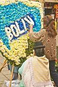Two women work on a blue white and yellow floral shield.