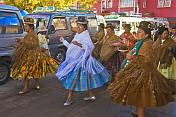 Women dancers walk through the streets in a traditional town festival.