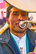 Sousaphone player in a brass band marching through the streets in a traditional town festival.