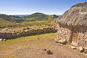 Thatched stone house and terraced farmland on the Isla del Sol in Lake Titicaca.