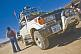 Man loads luggage on a Toyota 4WD Land Cruiser prior to crossing salt flats.