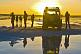 Tourists with Land Rover viewing the sunset on the Uyuni Salt Flats.