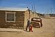 Woman and child walk past shell of car on street of adobe houses.