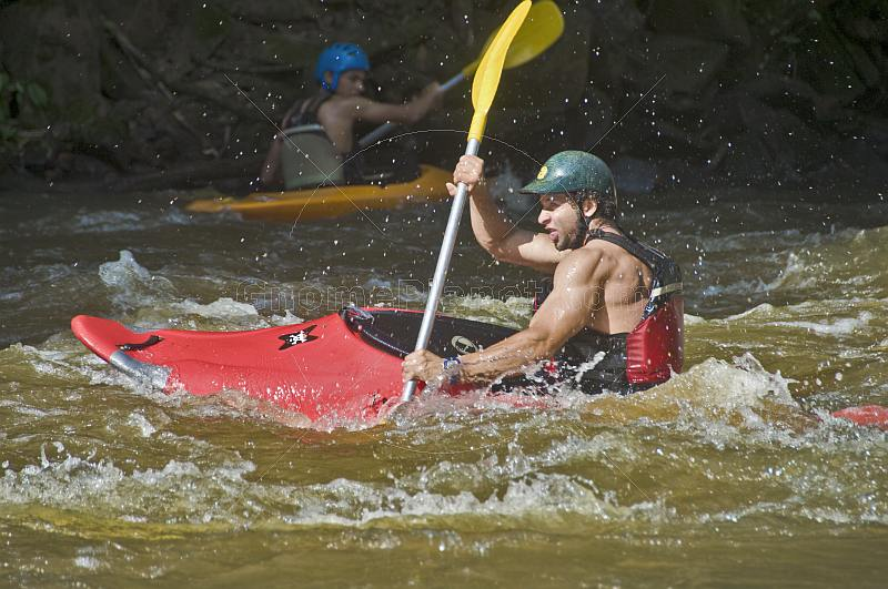 Canoeist in multi-colored kayak negotiates rapids.