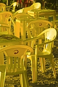Yellow plastic chairs and tables on the beach.