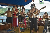 Rock band plays on board schooner in the waters of the Bahia Da Ilha Grande.