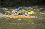 Canoeist in orange kayak negotiates rapids.