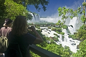 Travellers admire the waterfalls and jungle at the Iguazu Falls.