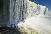 Travellers view the waterfalls cascading into the Iguazu River.
