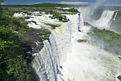 Water with rainbow cascades into the river at the Iguazu Falls.