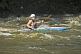Young canoeist in black kayak negotiates the rapids.