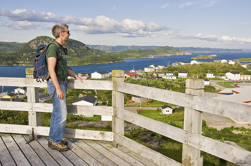 Male hiker looks out over the town to the ocean forests and mountains.