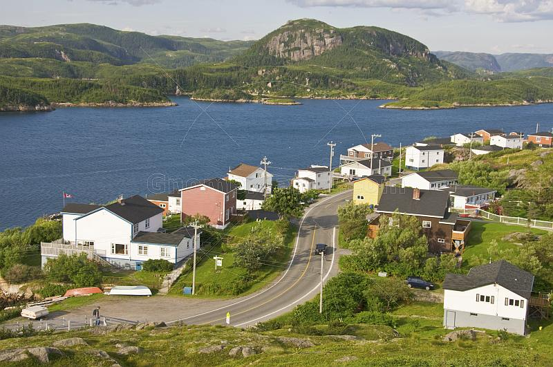 View over the town to the ocean inlet with coniferous forests and mountains.