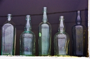 Antique drinks bottles in the window of a Curios shop.