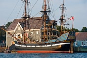 Replica pirate ship 'Hector' moored to the Pictou wharf, alongside colonial style buildings.