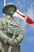 Bronze statue of Canadian soldier stands in front of National flag on memorial for World War one and two.