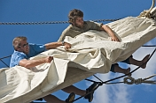 Two male crew members of the tallship 'Picton Castle' work aloft to stow sail.