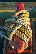 Red dock mooring bollard with white rope in early morning sunlight.