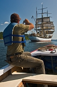 Man in small motor boat takes photo of the tallship 'Picton Castle' as she sets sail towards the ocean.