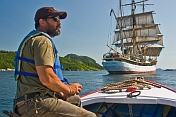 Man in small motor boat watches the square rigger \\'Picton Castle\\' as she sets sail towards the ocean.