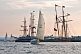 Image of Yachts race past moored tallships in Pictou Harbour.