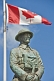 Image of Bronze statue of Canadian soldier stands under National flag on memorial for World War one and two.