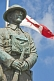 Image of Bronze statue of Canadian soldier stands in front of National flag on memorial for World War one and two.