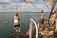 Image of Crew of the \\\\'Picton Castle\\\\' wait their turn to swing on a rope and swim in the ocean.